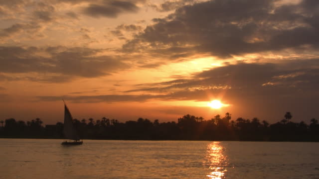 ws, silhouettes of felucca boat on nile river at sunset, egypt - 静かな情景点の映像素材/bロール