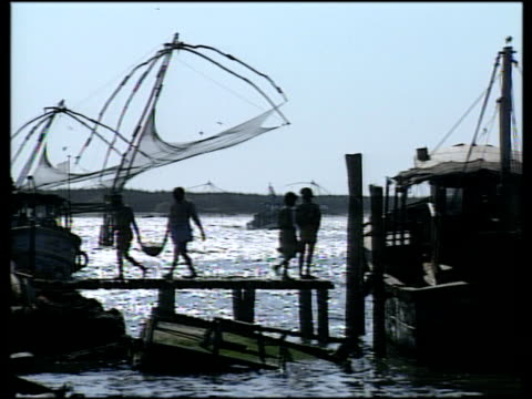 vídeos de stock e filmes b-roll de silhouettes of fishermen bringing in days catch from boats against dusk sky traditional chinese fishing nets in background drift in twinkling sea water cochin kerala - rede de pesca comercial