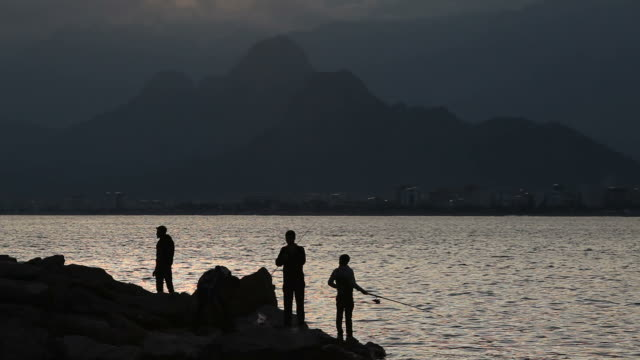 Silhouettes of fishermen in sunset
