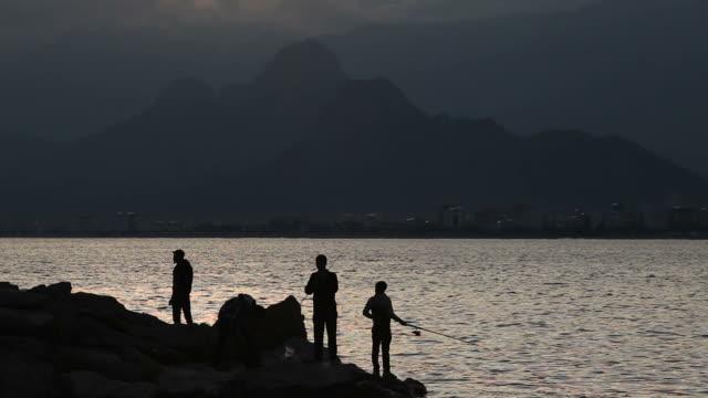 stockvideo's en b-roll-footage met silhouettes of fishermen in sunset - selimaksan