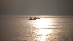 Silhouettes of fishing boats floating on the sunset sea