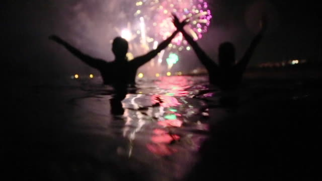 silhouettes of group of people taking a bath in the beach at night contemplating the colorful fireworks with nice colors and reflection on the water. - firework display stock videos & royalty-free footage