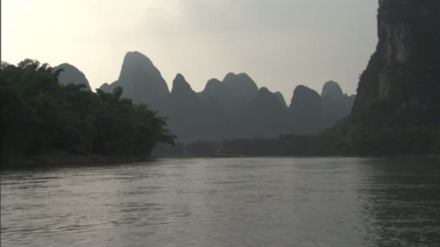 silhouettes of limestone peaks tower above the horizon near the li river on a cloudy day. - li river stock videos & royalty-free footage