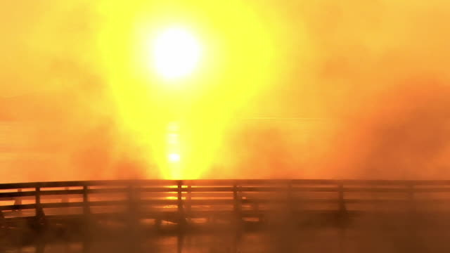 MS, Silhouettes of man crossing bridge at sunrise, steam raising from West Thumb Geyser Basin, Yellowstone National Park, Wyoming, USA
