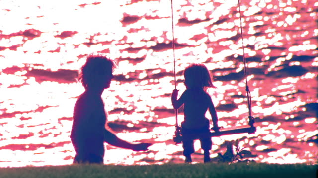 overexposed blue rear view silhouettes of man pushing girl toddler on swing / ocean in background / hawaii - overexposed stock videos & royalty-free footage