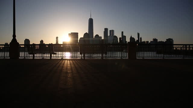 silhouettes of manhattan skyscrapers seen across hudson river at sunrise, from the waterfronts of jersey city and hoboken, nj, new york city, ny,... - silhouette stock videos & royalty-free footage
