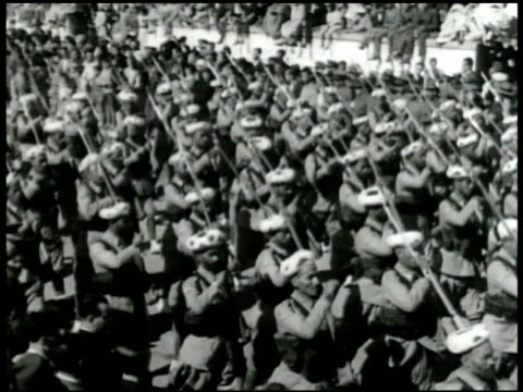 stockvideo's en b-roll-footage met silhouettes of many twin engine airplanes in flight overhead. moors moorish soldiers marching in parade formation in street. two officers standing... - 1936