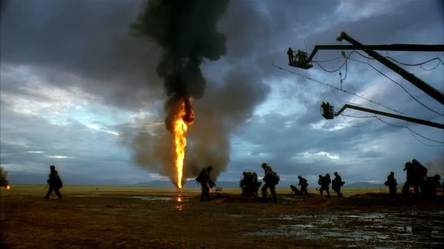 vidéos et rushes de ws, reenactment silhouettes of marines walking by burning oil wells, kuwait - décor de cinéma