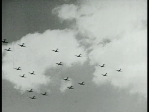 Silhouettes of military aircraft flying in formation of 3's World War II