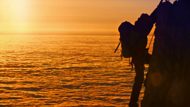 Silhouettes of mountaineers shaking hands on mountain top at sunset