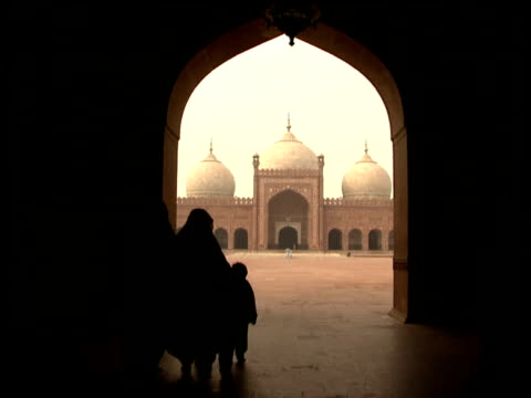 Silhouettes of Muslim women in black hijab accompanied by children walk through Moorish archway looks with view to courtyard and mosque in distance