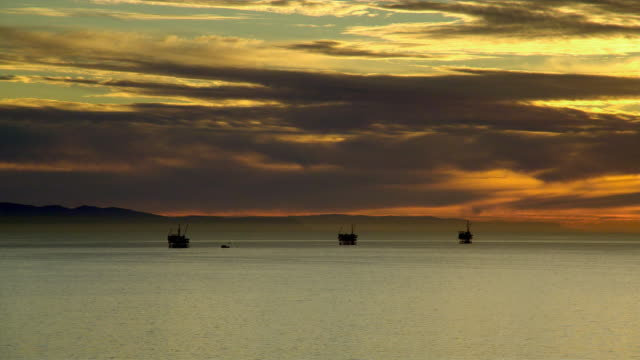 WS Silhouettes of oil rigs in ocean at sunset, Santa Barbara, California, USA