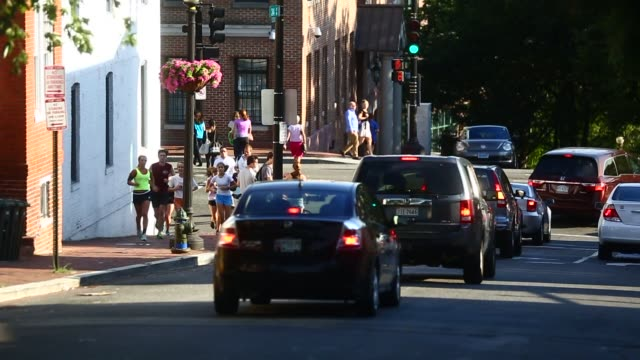 vidéos et rushes de silhouettes of pedestrians carry shopping bags on m street nw in the georgetown neighborhood of washington dc us vehicles drive on the francis scott... - georgetown washington dc