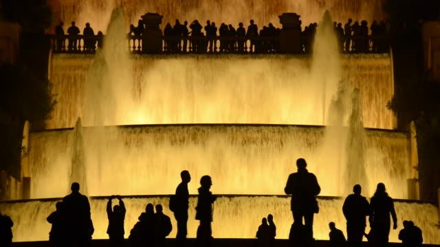 vídeos y material grabado en eventos de stock de ms silhouettes of people against magic fountain in barcelona illuminated at night / barcelona, catalunya, spain - contraluz