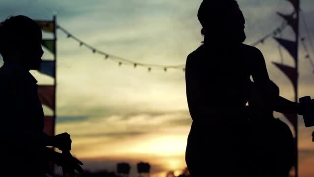 vídeos de stock, filmes e b-roll de silhuetas de pessoas dançando no festival - jogando se na multidão