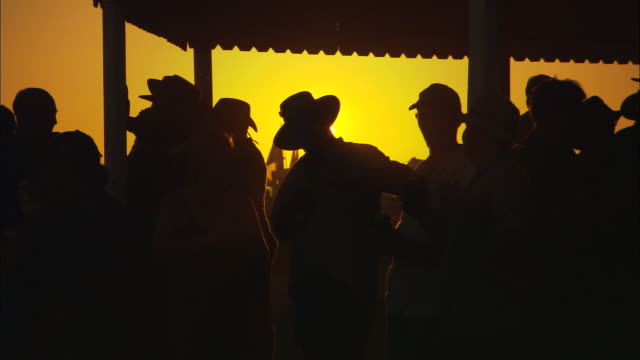 MS Silhouettes of people drinking and talking outside of pub at twilight, Birdsville, Queensland, Australia