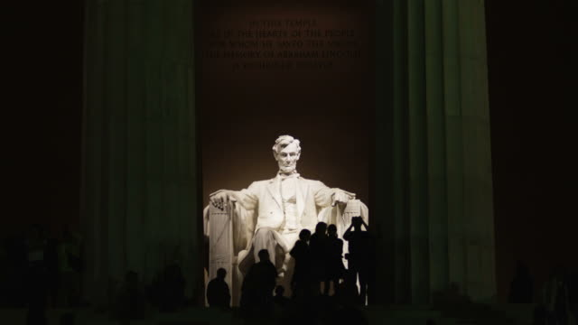ws silhouettes of people in front of abraham lincoln statue at lincoln memorial illuminated at night, washington d.c, usa - lincolndenkmal stock-videos und b-roll-filmmaterial