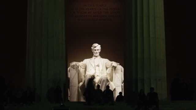t/l ws silhouettes of people in front of abraham lincoln statue at lincoln memorial illuminated at night, washington d.c, usa - abraham lincoln stock videos & royalty-free footage