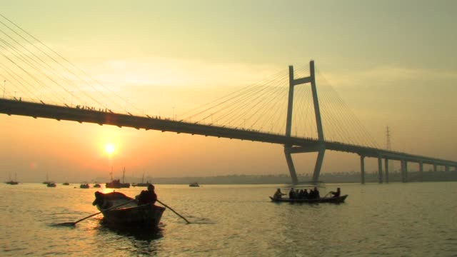 MS, Silhouettes of people in rowing boat on Ganges river, 2nd Yamuna Bridge in background, sunrise, Allahabad, Uttar Pradesh, India