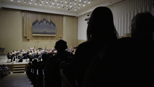 Silhouettes of people in the audience listening to a classical music concert.