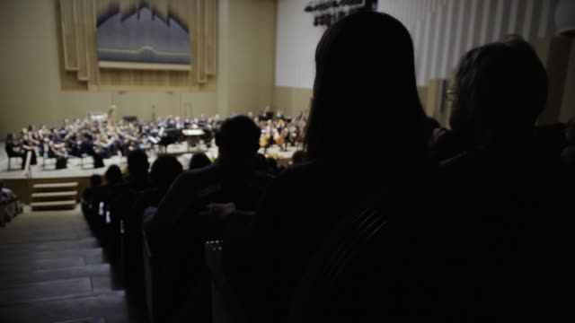 vidéos et rushes de silhouettes of people in the audience listening to a classical music concert. focus is on the foreground - plan large