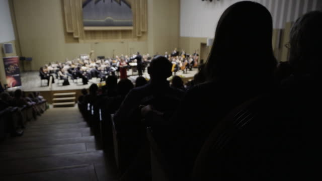 silhouettes of people in the audience listening to a classical music concert. focus is on the foreground - orchestra stock videos & royalty-free footage