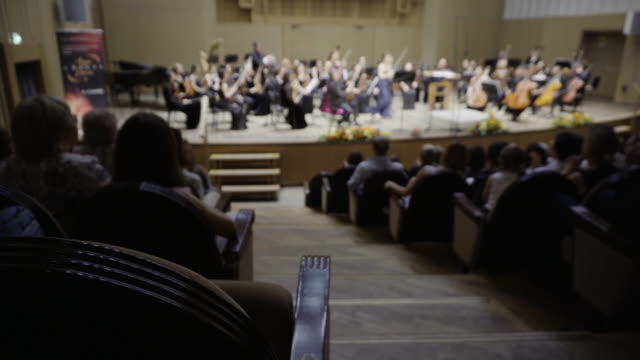 silhouettes of people in the audience listening to a classical music concert. focus is on the foreground - classical stock videos & royalty-free footage