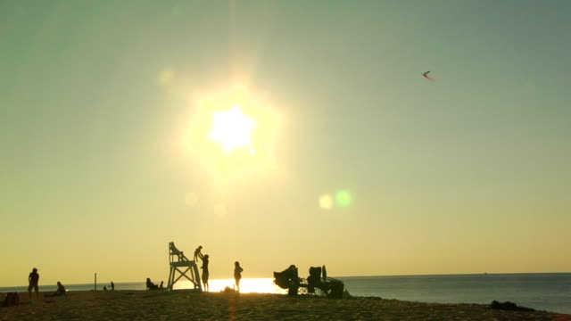 ws, silhouettes of people on beach, provincetown, massachusetts, usa - cabina del guardaspiaggia video stock e b–roll