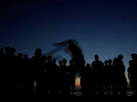 MS, Silhouettes of people performing capoeira on Jericoacoara beach at dusk, Brazil