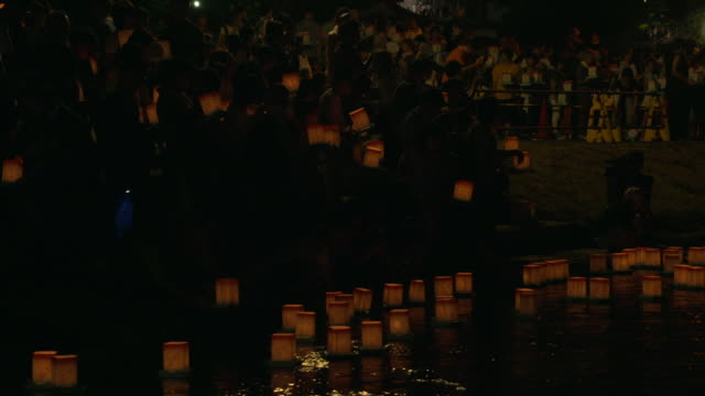 Silhouettes of people placing lanterns on the Kuzuryu  River