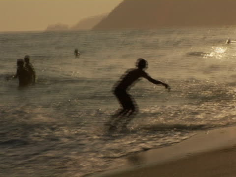WS, ZI, Silhouettes of people relaxing on Ipanema beach at sunset, Rio de Janeiro, Brazil