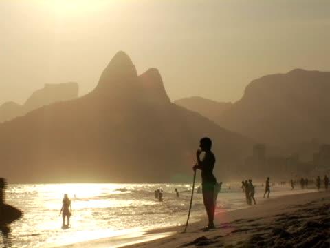 ws, silhouettes of people relaxing on ipanema beach at sunset, rio de janeiro, brazil - viraggio monocromo video stock e b–roll