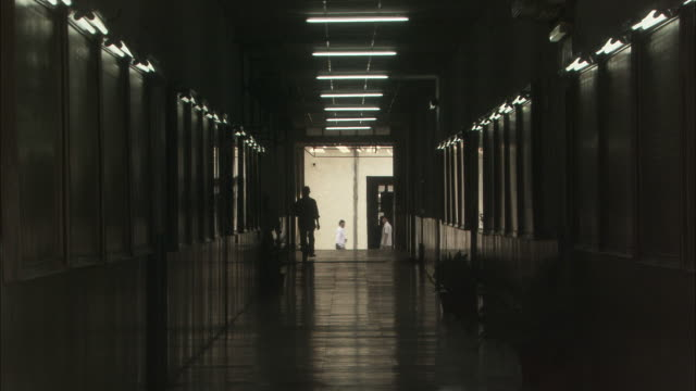silhouettes of people walk along dimly lit corridor available in hd. - low lighting stock videos & royalty-free footage