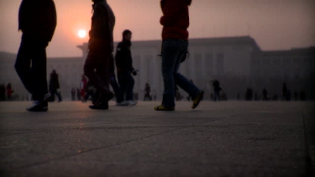 slo mo ws silhouettes of people walking in front of great hall of the people in tiananmen square at sunset, beijing, china - tiananmen square stock videos & royalty-free footage