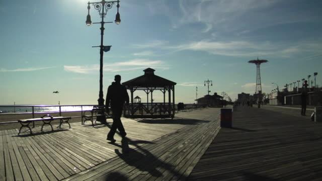 ws, silhouettes of people walking on boardwalk, coney island, new york city, new york, usa - coney island brooklyn stock videos & royalty-free footage