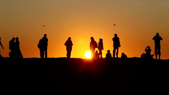 WS Silhouettes of people watching sunset at Cape St. Vincent (Cabo de Sao Vicente) / Algarve, Portugal
