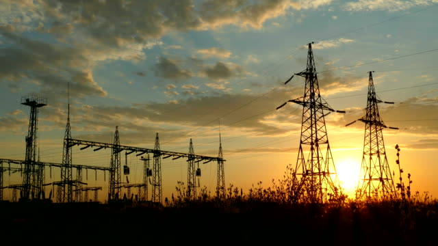 Silhouettes of power lines at sunset