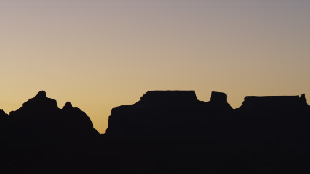 vídeos de stock e filmes b-roll de ws pan silhouettes of rocks against sky at sunset / lake powell, utah, usa - lago powell