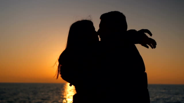 silhouettes of romantic couple meeting at sunset - love stock videos & royalty-free footage