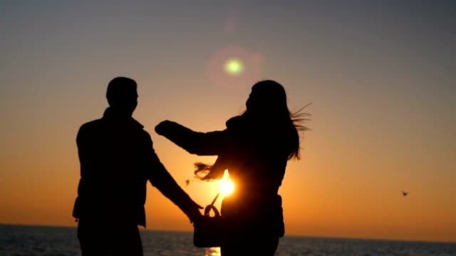 Silhouettes of romantic couple meeting at sunset