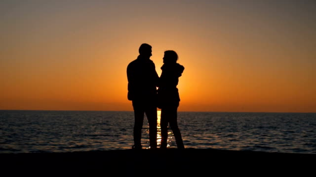 Silhouettes of romantic couple turning around at sunset