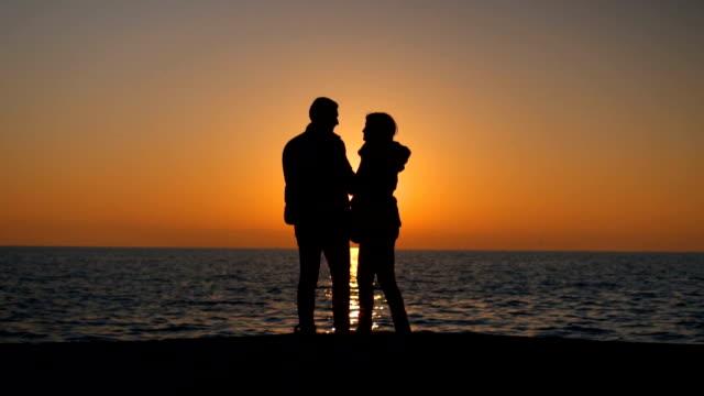 vídeos de stock, filmes e b-roll de silhuetas de par romântico, dando a volta ao pôr do sol - céu romântico