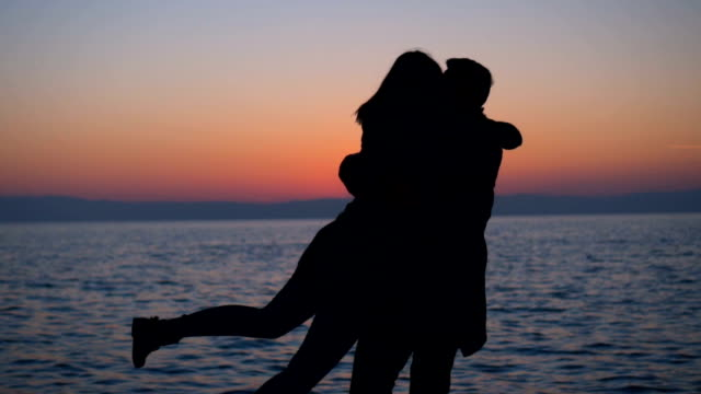 Silhouettes of romantic couple turning around in sunset