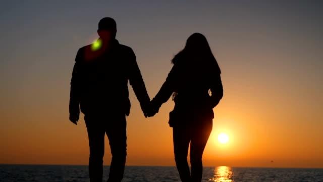 夕暮れ歩くロマンチックなカップルのシルエット - 逆光点の映像素材/bロール