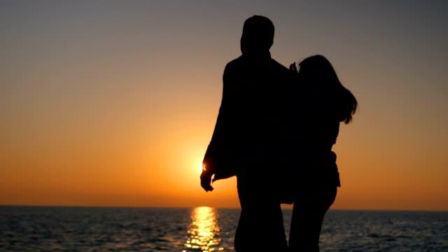silhouetten von romantisch zu zweit wandern bei sonnenuntergang - gemeinsam gehen stock-videos und b-roll-filmmaterial