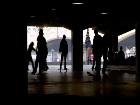 silhouettes of skateboarders under concrete walkways of south bank centre london - 1999 stock videos and b-roll footage