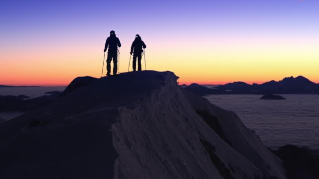 vidéos et rushes de silhouettes de tourers de ski passant par la crête de montagne au crépuscule - lampe frontale