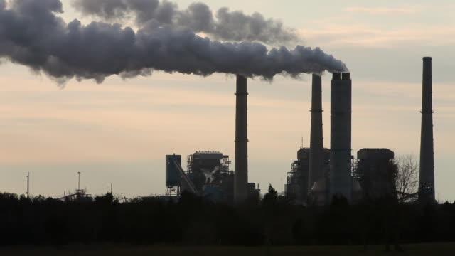 silhouettes of smoke stacks of coal plant at sunset - smoke stack stock videos & royalty-free footage