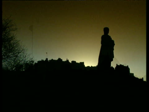 Silhouettes of statue and Edinburgh Castle turrets with Union Jack on pole
