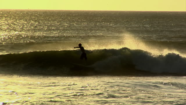 ws, pan, silhouettes of surfers on waves at sunset, nosara, guanacaste, costa rica - nosara stock videos and b-roll footage
